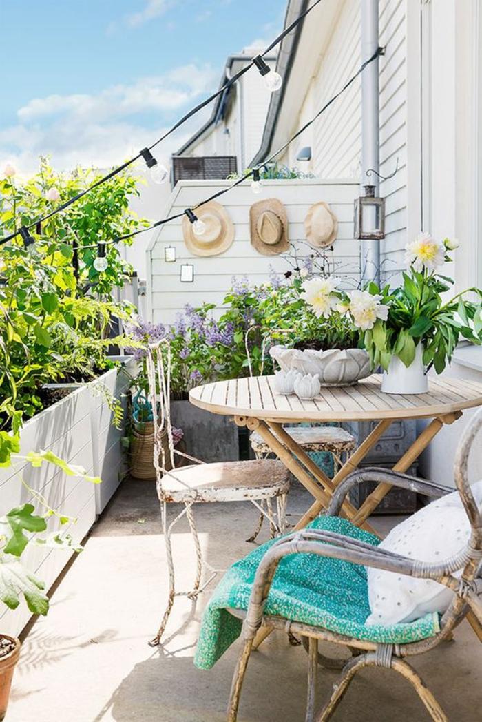 idee amenagement terrasse en style bohème, balcon fleuri, decoration jardin terrasse, meubles vintage, trois chapeau de paille accrochés au mur blanc