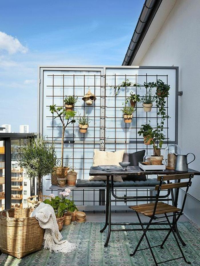 balcon fleuri, mur porte-plante avec une dizaine de pots avec des fleurs, carrelage motifs orientaux en vert et blanc, meubles pliables de jardin IKEA, gros panier de paille tressée
