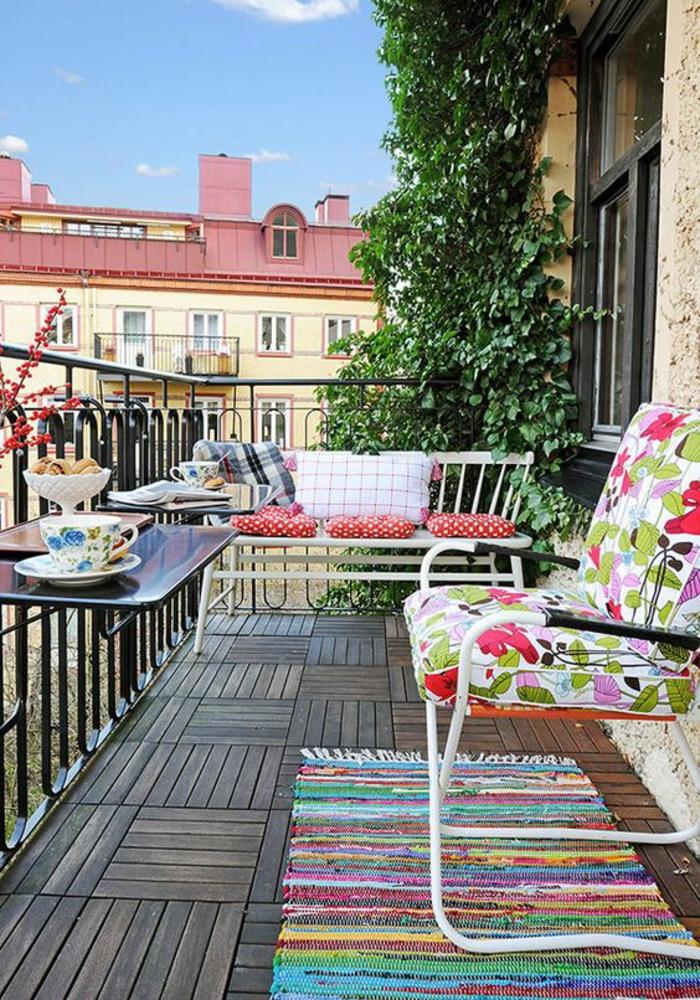 idee deco terrasse en style bohème, tapis rectangulaire en style ethnique, sol recouvert de bois parquet original, table pliable, garde-corps en métal noir