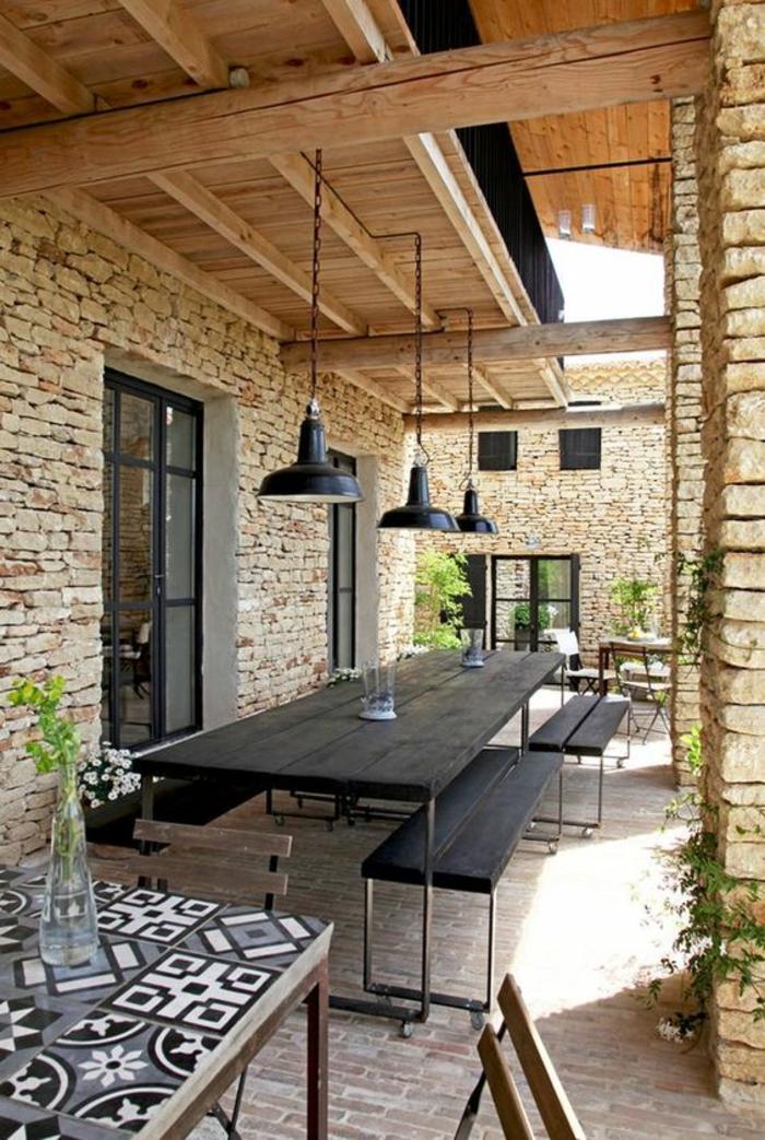 une terrasse en longueur, decoration jardin terrasse avec des bancs en bois noir, table avec plan en mosaïque gris et blanc, trois luminaires en style industriel en métal noir, sol couvert de briques marron