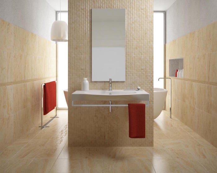 salle de bain beige marbrée carrelée sur le sol et les murs avec mur séparateur pour baignoire