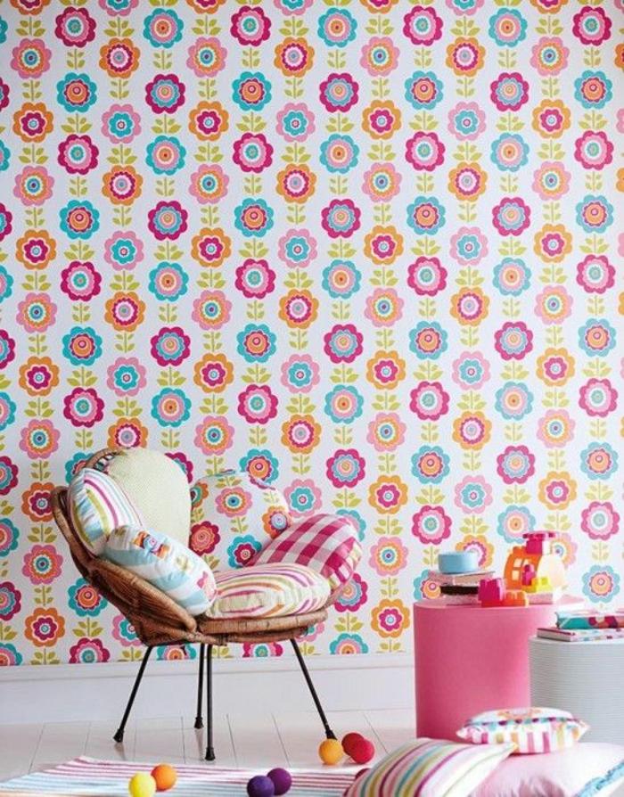 décoration murale salon, tapis mural avec des effets fleurs en rouge-rose et vert, fauteuil de jardin en rotin avec des pieds en métal noir, coussins carrés aux rayures verticales couleurs vives