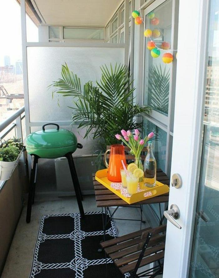espace convivial, decoration terrasse exterieur, barbecue en vert et noir, tapis rectangulaire en noir et blanc motifs cordes marines, meubles pliables IKEA en marron foncé, guirlande avec des de boules lanternes multicolores, palmier dans un angle