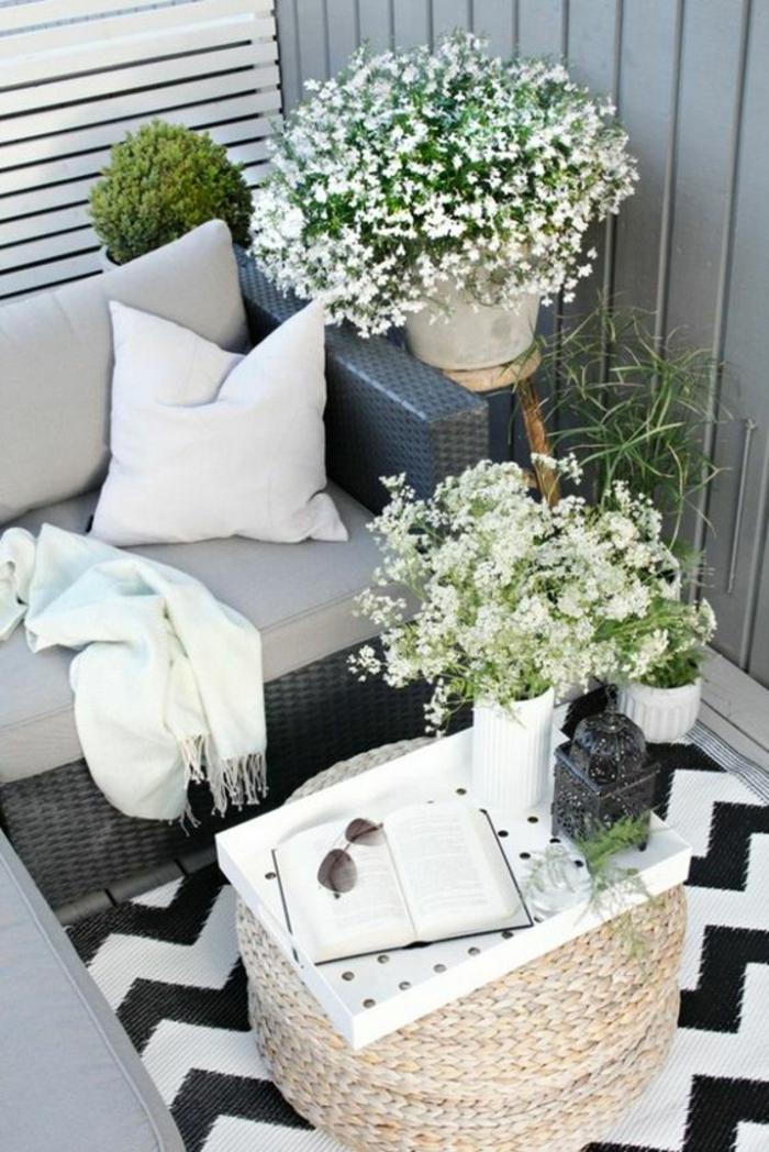coin de terrasse avec canapé en rotin noir synthétique, table ronde en canne tressée claire, decoration terrasse exterieur, tapis motifs graphiques noirs et blancs