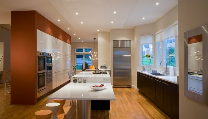 cuisine originale, ilot central avec table, mur équipé d'électroménager, tabourets minimalistes