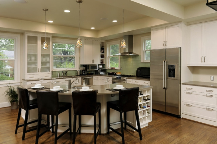 modele de cuisine avec ilot, chaises noires situées autour de la table courbée, rangement astucieux