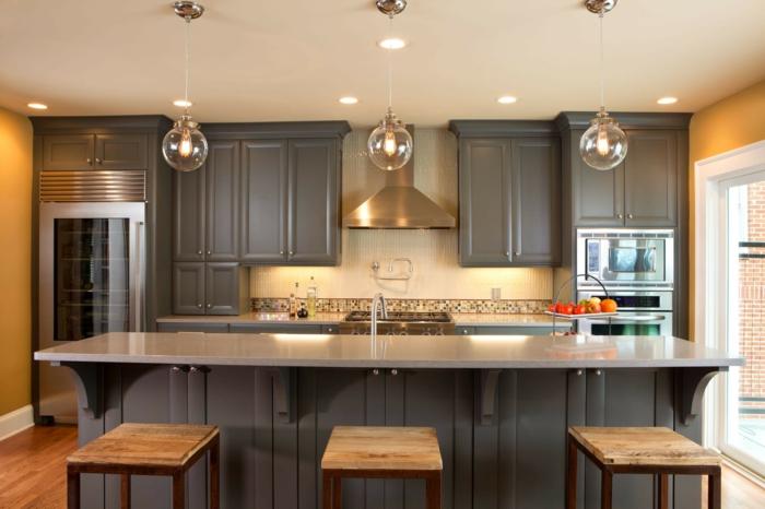 plan de travail central ilot, tabourets en bois, lampes rondes suspendues, cabinets gris