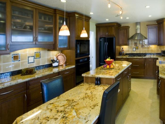 comptoir en marbre avec table longue, lampes suspendues beiges, cabinets avec vitrines, sol beige