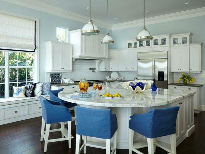 modele de cuisine avec ilot central, chaises bleues, ilot et table en forme courbée, murs bleus, grande fenêtre et banquette
