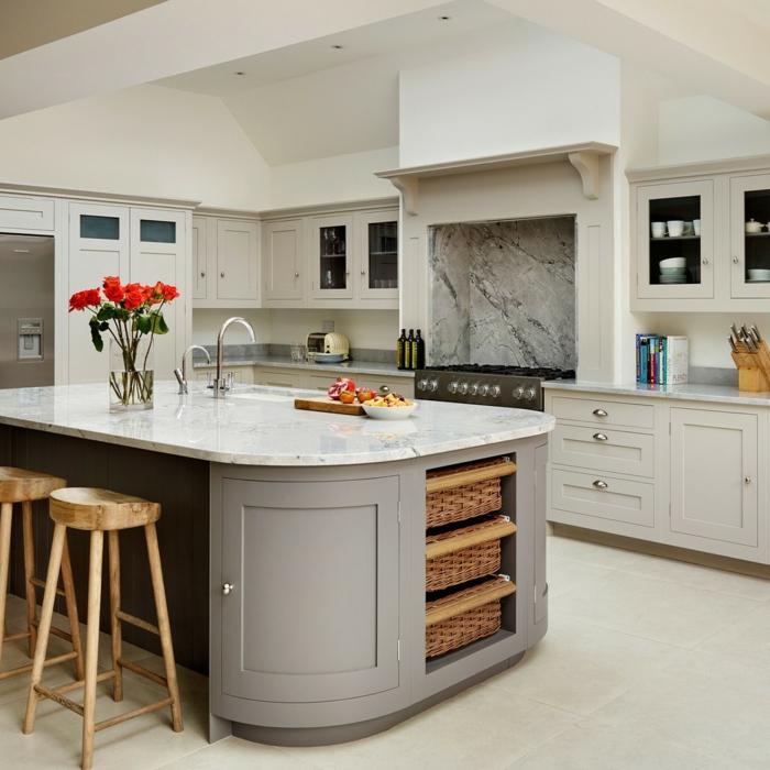 cuisine grise aux lignes sobres, un plan de travail courbé avec évier et espace dinatoîre, tabourets de bois,