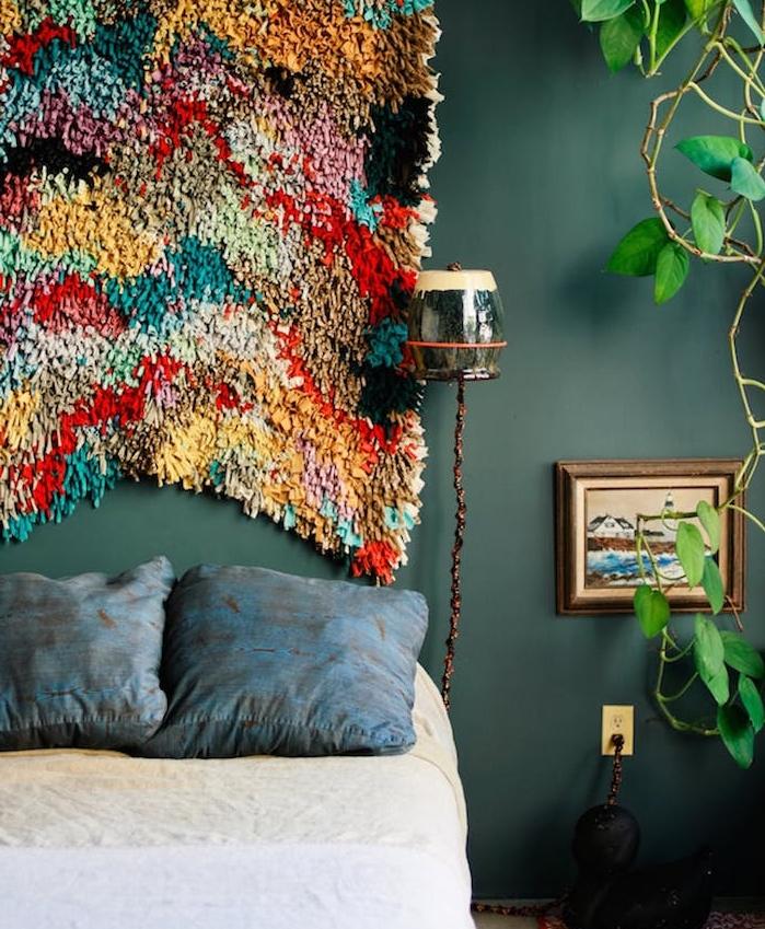 exemple de tete de lit tissu coloré, mur vert de gris foncé, linge de lit beige et blanc et coussins décoratifs bleus, plante verte