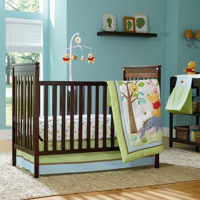 aménagement chambre nouveau-né aux murs bleu clair et plancher de bois clair, design thématique avec mobile bébé à design Winnie l'ourson