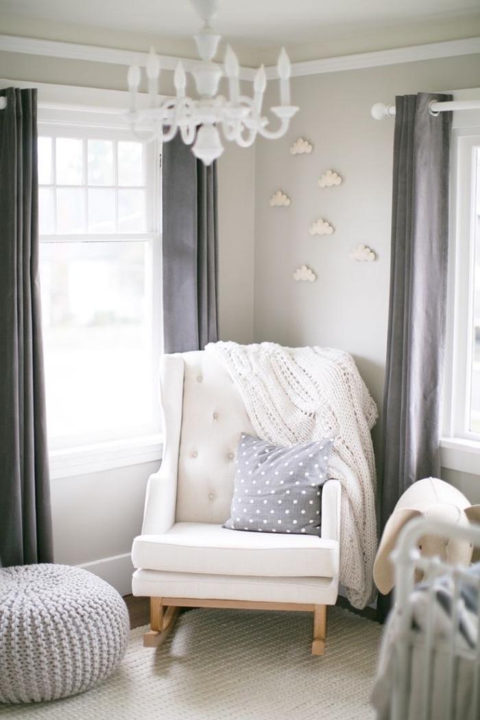 coin de repos dans une pièce nouveau-né aux murs beige avec un fauteuil à dos boutonné blanc et pieds de bois