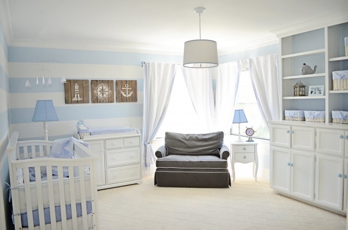 exemple de design bicolore en blanc et bleu clair dans une pièce de nouveau-né avec rideaux longs et meubles de bois blancs