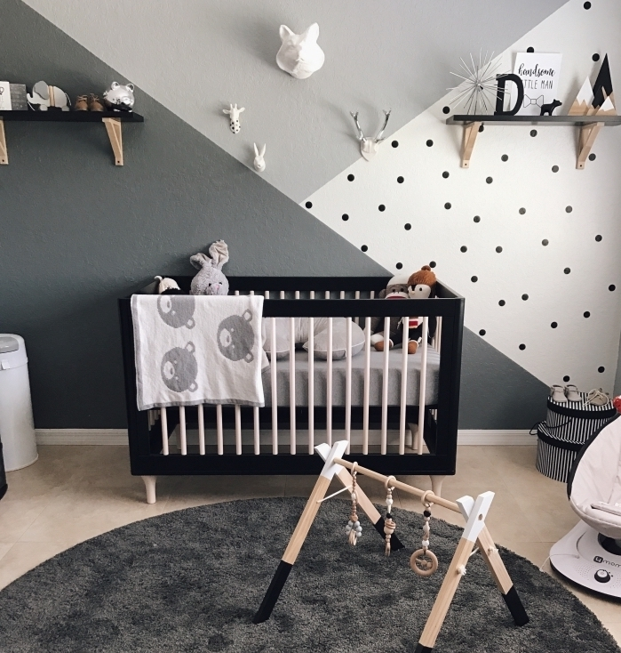 modèle de chambre bébé mixte avec décoration murale en peinture gris clair et gris foncé combiné avec pan de mur blanc à points noirs