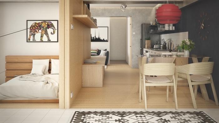 exemple aménagement studio 25m2 aux murs blancs avec meubles de bois clair et déco de pan de mur en peinture gris anthracite