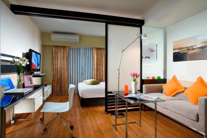 design moderne aux murs blancs et plancher de bois marron avec meubles à finitions noires et accents colorés