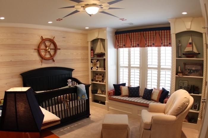aménagement de pièce enfant sur le thème marine avec revêtement mural en bois clair et lit-bébé noir sur plancher beige