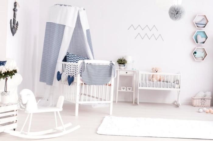 déco de chambre bébé aux murs blancs avec lit bébé blanc et bleu marine, objets décoratif en blanc et bois