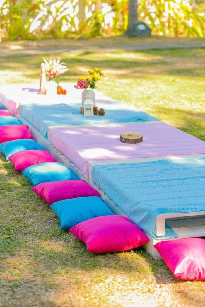 amenagement exterieur, deco jardin pas cher, tables basses en palettes avec des nappes en couleurs pastels, coussins pour s'asseoir en fuchsia et bleu pastel