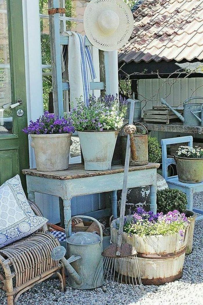 decorer son jardin, amenagement jardin, table et chaises en bois peint en bleu pastel, fauteuil en rotin tressé, chapeau de paille suspendu