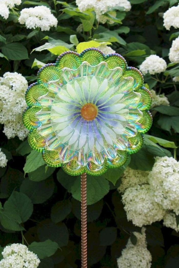 une fleur en plastique verte comme deco jardin pas cher, surface brillante qui reflète la lumière du soleil, amenagement exterieur, amenagement jardin paysager