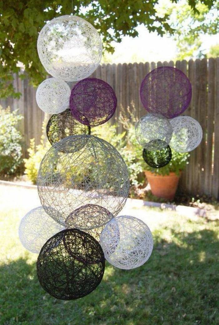 des boules tressées transparentes de toute taille et couleur suspendues aux branches d'un arbre, décorer son jardin, jardin deco, ambiance ludique