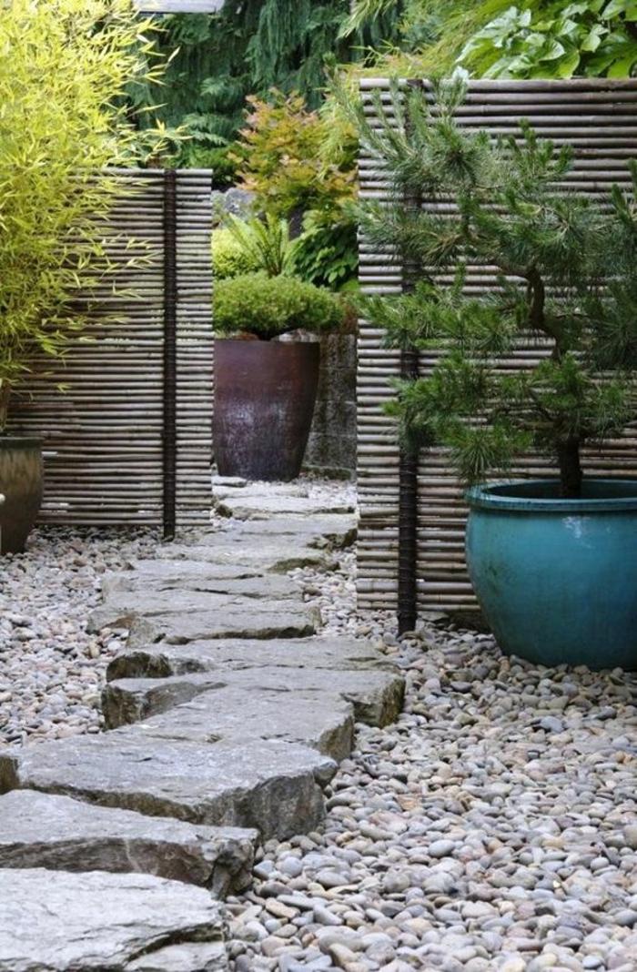 amenagement exterieur avec des grands pots de plantes vertes, grandes pierres grises organisées comme un petit chemin irrégulier, jardin paysager en style asiatique