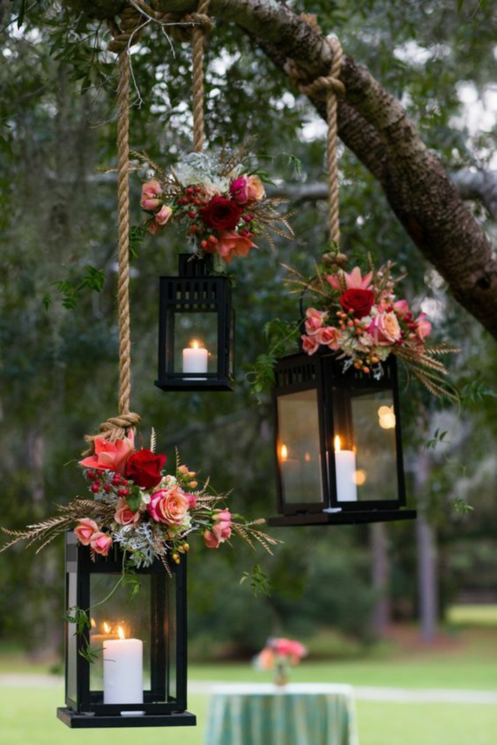 amenagement exterieur, trois lanternes en métal noir avec des bougies blanches, accrochées avec des cordes aux branches d'un arbre, décorer son jardin avec du style