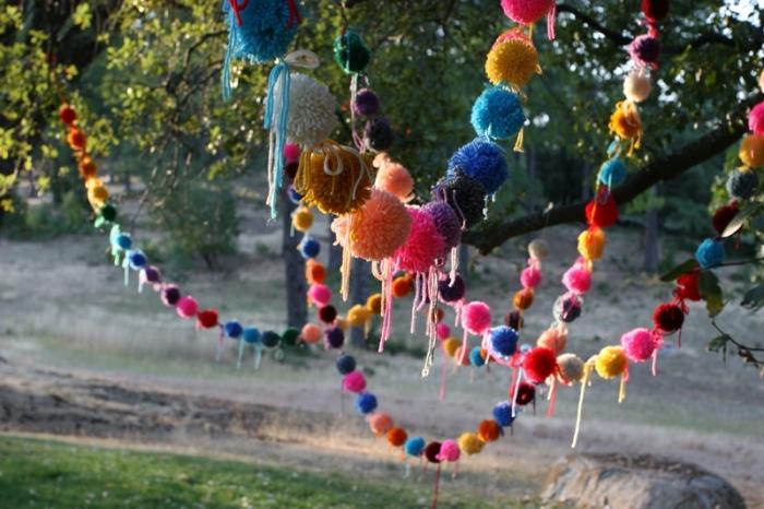 comment décorer son jardin pour une fête ou anniversaire, modèle de guirlande colorée avec pompons de laine