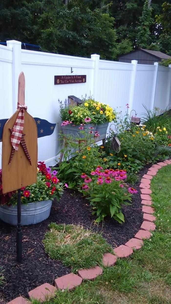 jardin paysager, jardin deco, amenagement exterieur, grandes pierres peintes en rose, déco jardin récup, fleurs roses, cintre en bois peint en blanc