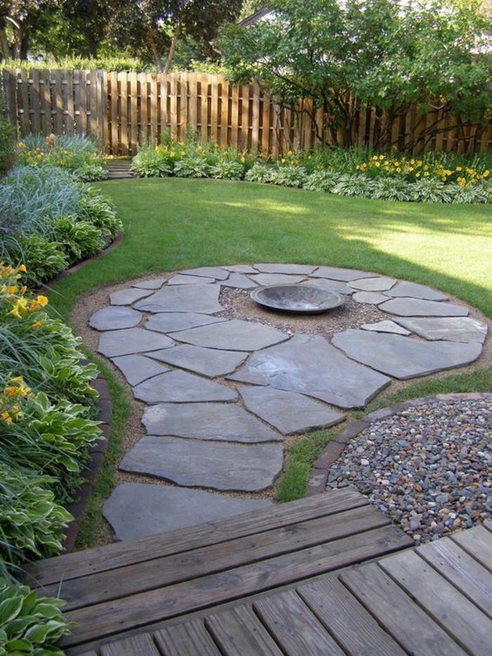 motif décoratif dans le jardin, décorer son jardin, éléments en pierre en formes de cercles, plantes vertes et fleurs jaunes, jardin paysager