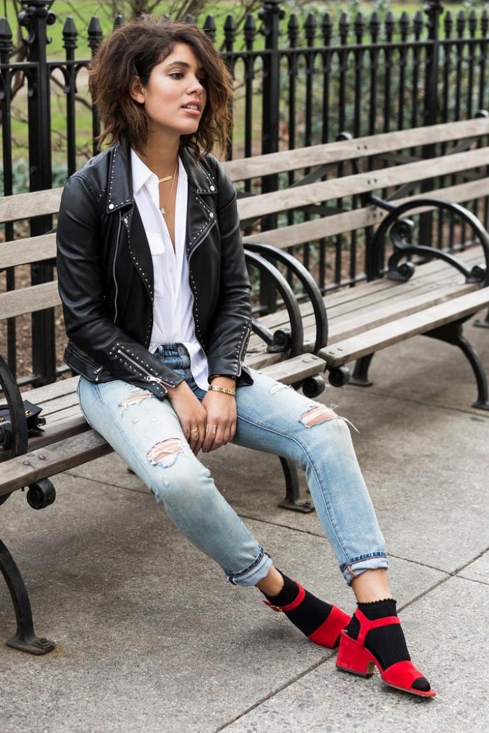 look rock chic avec paire de jeans déchirés clairs combinés avec veste en cuir noir à design studs, modèle de sandales rouges portées avec chaussettes noires