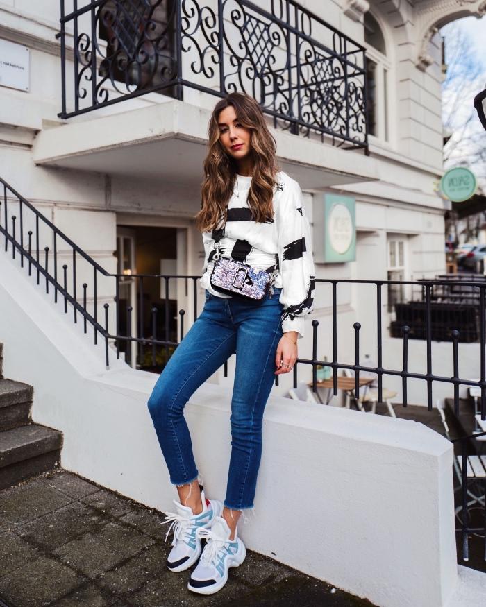 vision chic et sportive avec blouse à design rayé en blanc et noir porté avec paire de jeans clairs et une paire de dad sneakers blancs