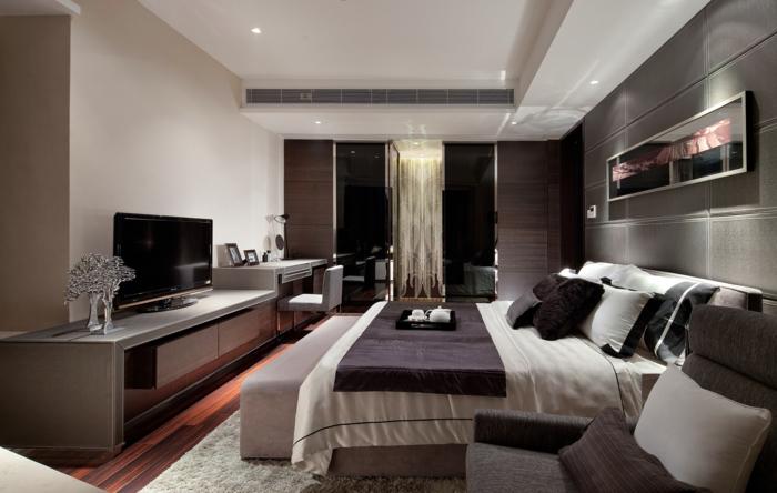 chambre monochrome, grand meuble de tv devant un grand lit, rideaux noirs et blancs