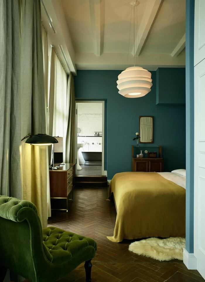 mur bleu, plafonnier blanc, fauteuil vert vintage, parquet chevron, peinture murale bleue