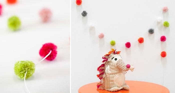 petit doudou fabriqué avec tissu de couleurs différentes en forme de hérisson, déco chambre enfant avec guirlande en pompons