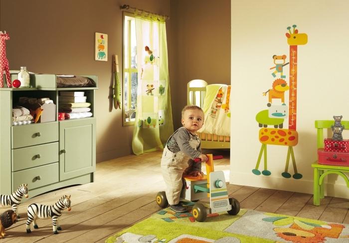 design intérieur dans une pièce enfant aux murs taupe et jaune pâle avec dessin girafe et plancher de bois