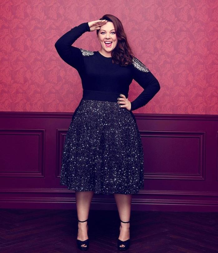 jupe grande taille noire et blouse noire à épaules gris, chaussures à talon noires, cheveux chatain sur le coté