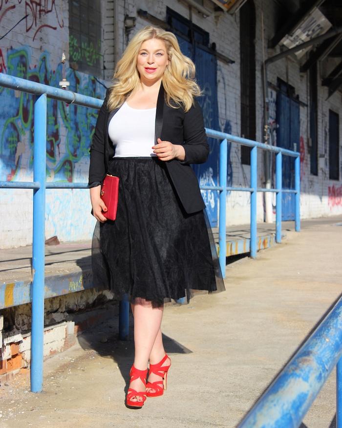 jupe grande taille évasée en noir et tulle, tee shirt blanc et veste noire, chaussures et pochette femme rouge