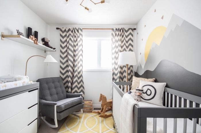design de la chambre bébé en couleurs blancs et noirs de style minimaliste avec accessoires de bois et aux accents en gris