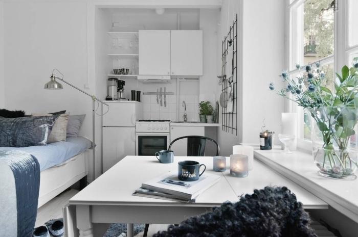 ambiance cozy dans un studio étudiant avec grande fenêtre aménagé avec petite cuisine blanche et grand lit