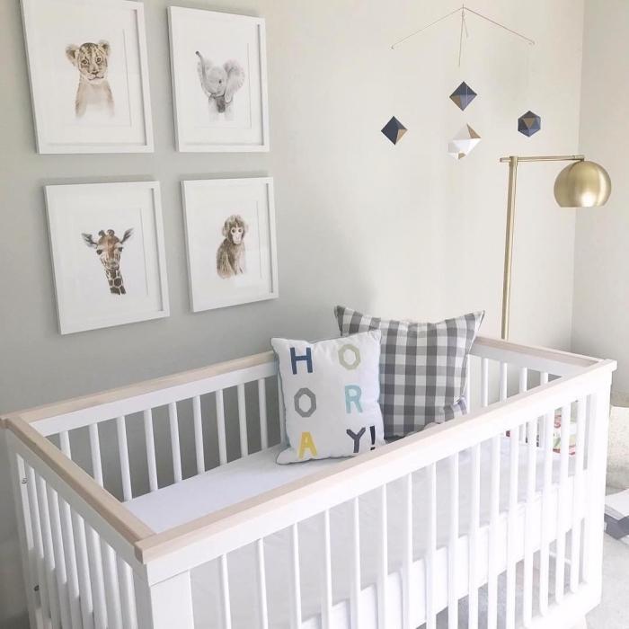 modèle de mobile bébé à design cristaux au-dessus d'un lit bébé blanc et bois avec coussins décoratifs et lampe sur pied dorée