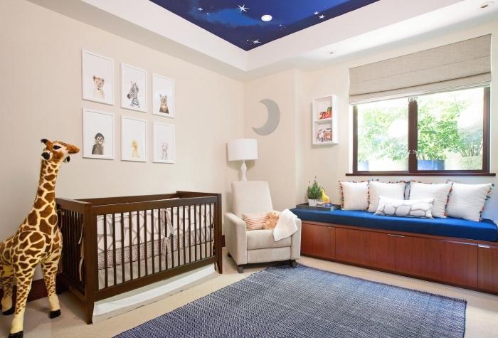 banc sous fenêtre avec rangement de bois et plusieurs coussins blancs pour un coin de repos dans la chambre nouveau-né