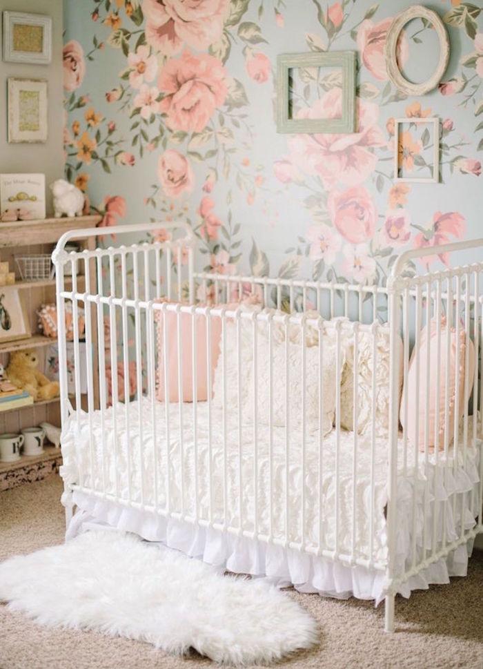 chambre pour bébé fille avec lit à barreaux et tapisserie fleurie à roses