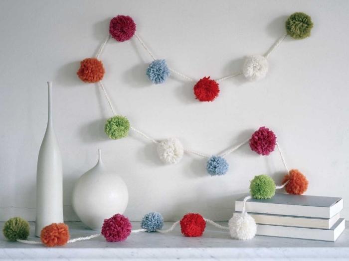 décoration stylée pour le salon aux murs blancs avec vase design blanc et guirlande fait main en boules de laine