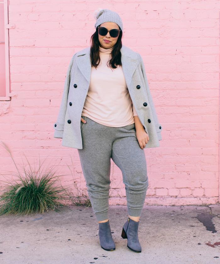 exemple de vêtements femme grande taille avec un tee shirt rose clair, manteau femme gris, pantalon de sport gris foncé, bottines et chapeau gris
