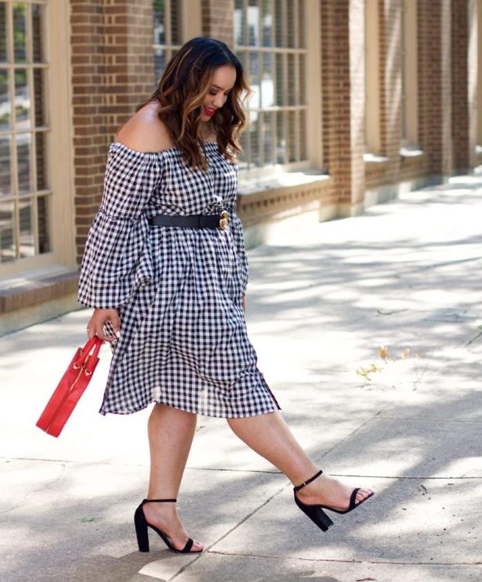 look femme stylé, robe noir et blanc, ceinture noire, chaussures à talons noirs, sac à manin rouge, cheveux mèches blondes
