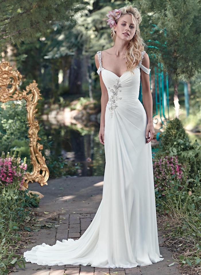robe de mariée longue champetre avec un motif floral de coté et bretelles tombantes, coiffure avec fleur