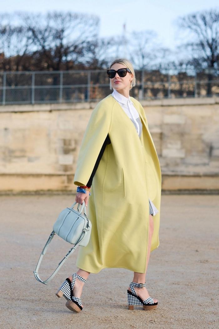 élégance femme en manteau ultra long de couleur jaune pastel combinés avec paire de sandales tendance en blanc et noir